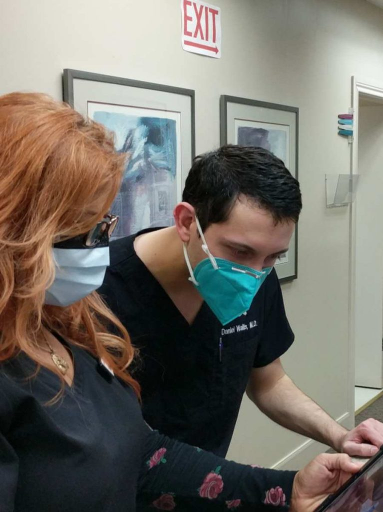 Dermatologist Dr. Daniel Wallis review chart notes after skin exam on an ipad.