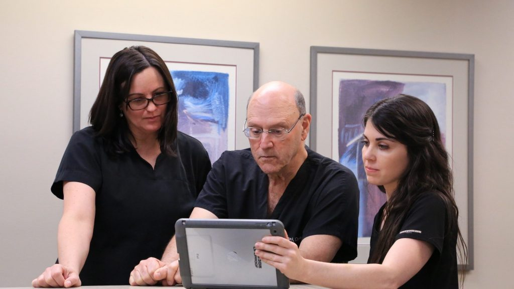 Dr. Steven A. Davis and PAs examining a medical chart on an ipad