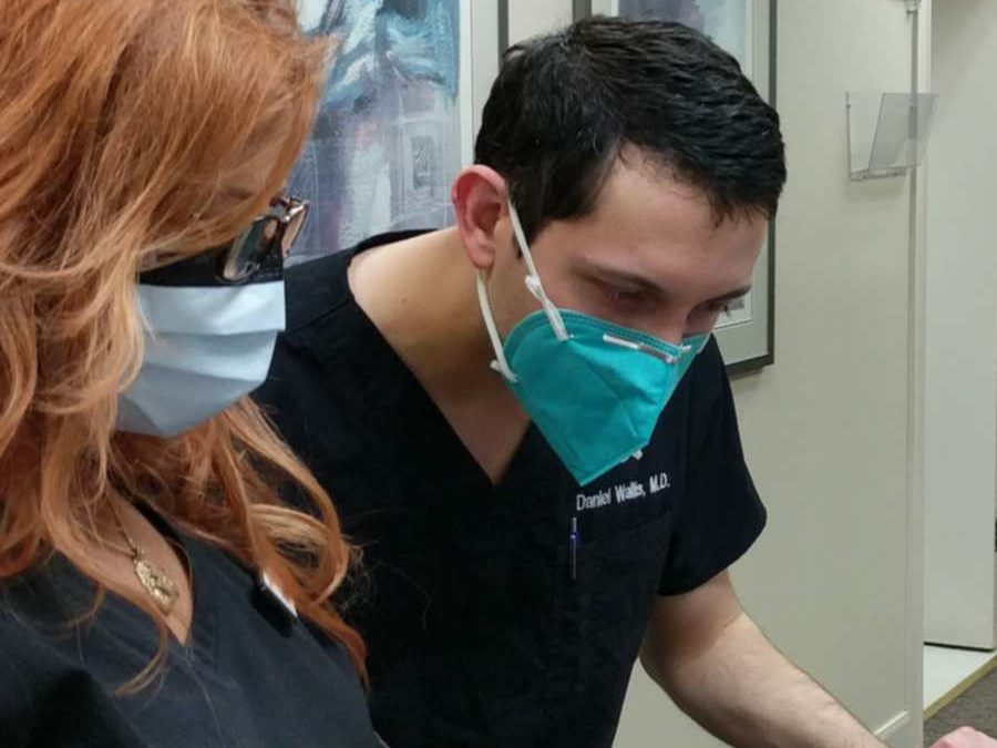 Photo of Dr. Daniel Wallis Examining a patient chart at Dermatology and Laser Center of San Antonio